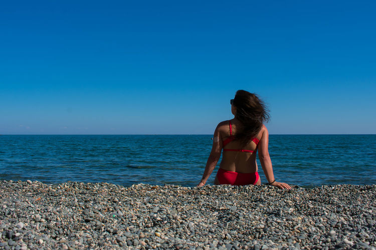 Sea Water Horizon Over Water Horizon Sky Beach Real People Land Blue Scenics - Nature Lifestyles Rear View One Person Leisure Activity Beauty In Nature Clear Sky Tranquility Tranquil Scene Nature Hairstyle Outdoors