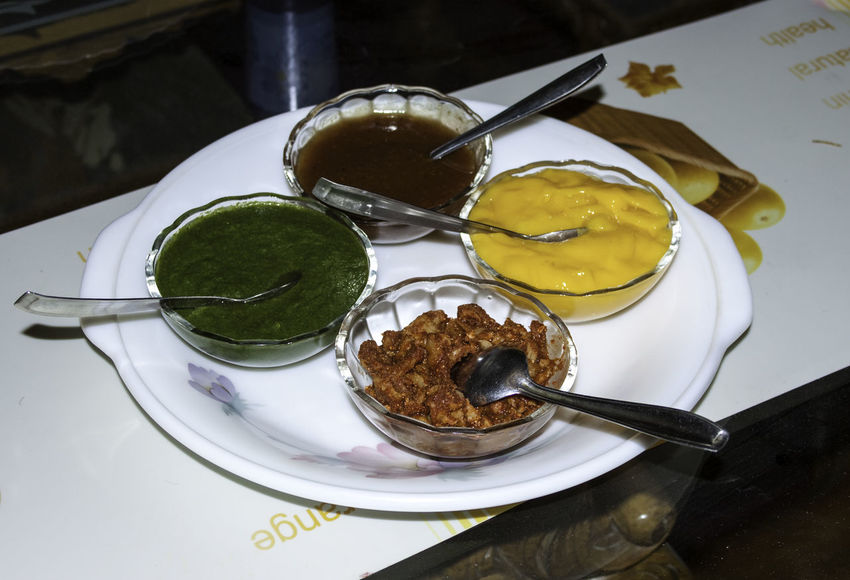 Several different condiments (mint, mango, others) in bowls on a white plate on a table. We were at a fancy restaurant and all these condiments were kept in a bowl, available for anybody to use. In Indian cuisine, these chutneys or dips play an important role in adding a bit of spice or a different touch to the meal. Chutneys Condiments  Accessories Chutney Close-up Food Food And Drink Freshness Indoors  No People Plate Ready-to-eat Table