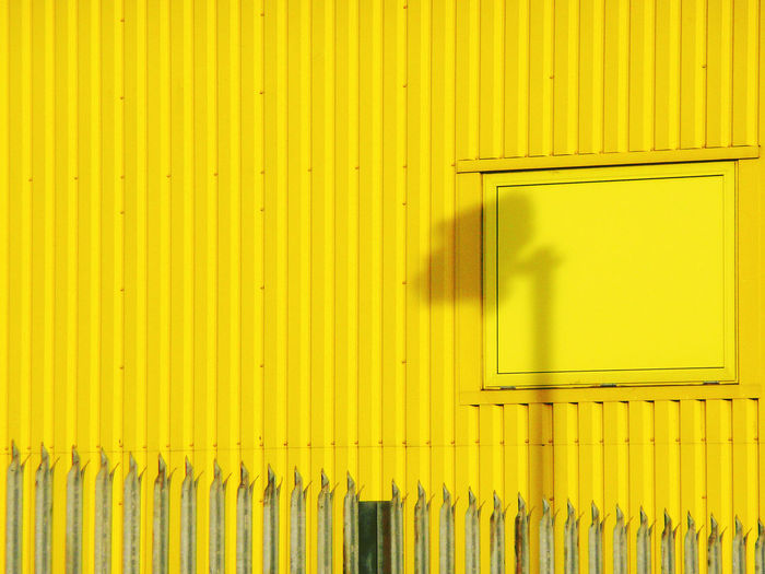 Shadow Of Security Camera On Yellow Wall