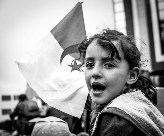 Portrait of girl holding flag at event
