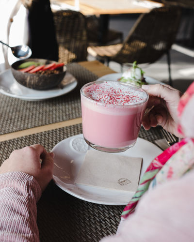 Food And Drink Human Hand Drink Hand Real People Refreshment One Person Human Body Part Holding Table Lifestyles Food Freshness Coffee Women Adult Cup Leisure Activity Indoors  Glass Body Part Finger Breakfast Pink Color