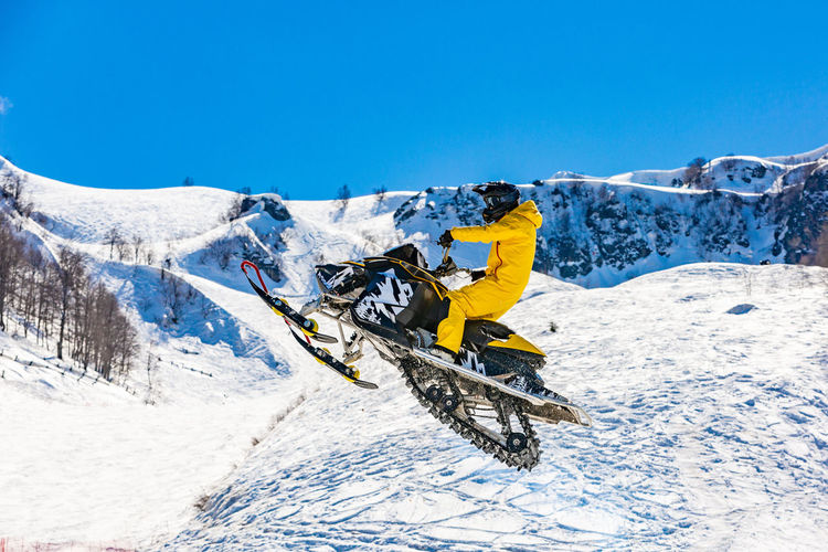 Person riding motor vehicle on snowcapped mountain against clear blue sky