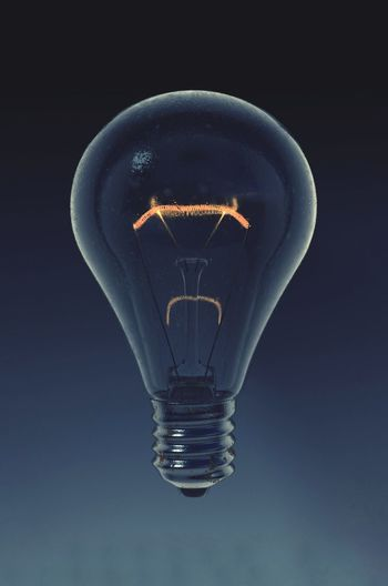 Close-up of light bulb levitating against gray background