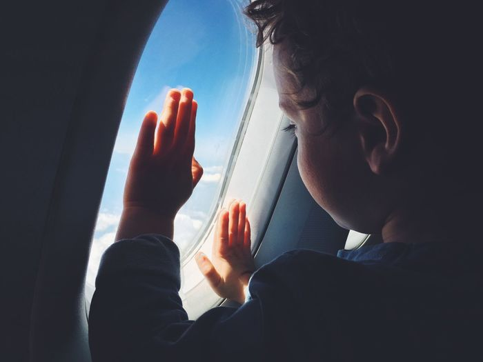 A young boy looks out of an aeroplane window. Person Window Transportation Communication Mode Of Transport Holding Person Human Finger Day Sky Scenics flight Flying window seat Single child Watching Looking Air Travel  IPhone