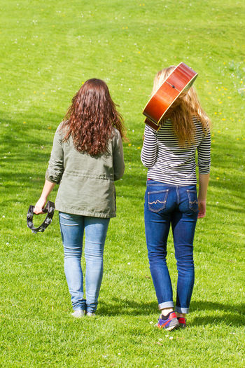 Two girls with instruments walking on a meadow Freedom Fun Happiness Happy Music Woman Education Friendship Girl Girls Grass Guitar Instrument Jeans Leisure Activity Music School Musician Outdoors People Rear View Relax Teenager Two People Walking Young Adult