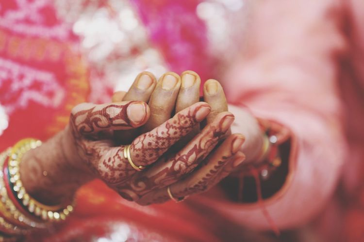 Midsection of bride and groom touching hands