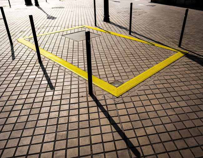 High angle view of road marking on paving stone