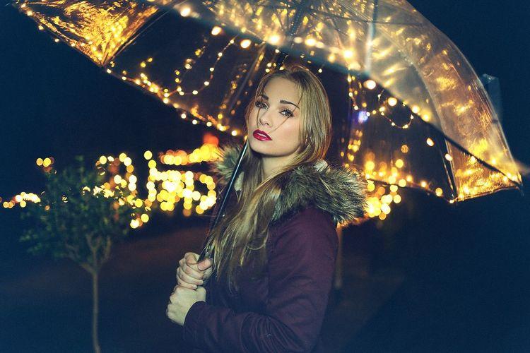 Woman in illuminated christmas tree at night