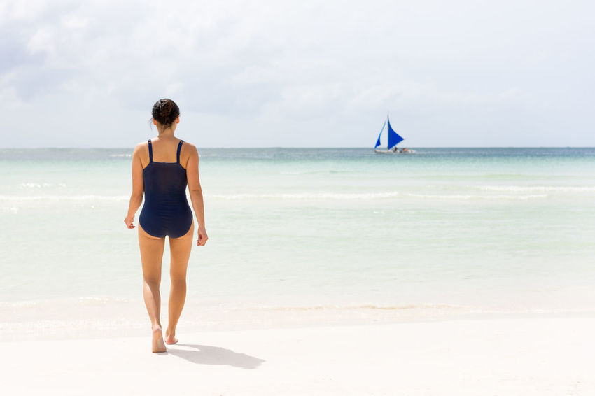 Young female walks out to the clear empty sea of Boracay beach. Alone Philippines The Week On EyeEm Beach Boracay Empty Horizon Minimalism One Person Real People Rear View Sailing Sailing Boat Sea Simple Walking White Sand Young Adult