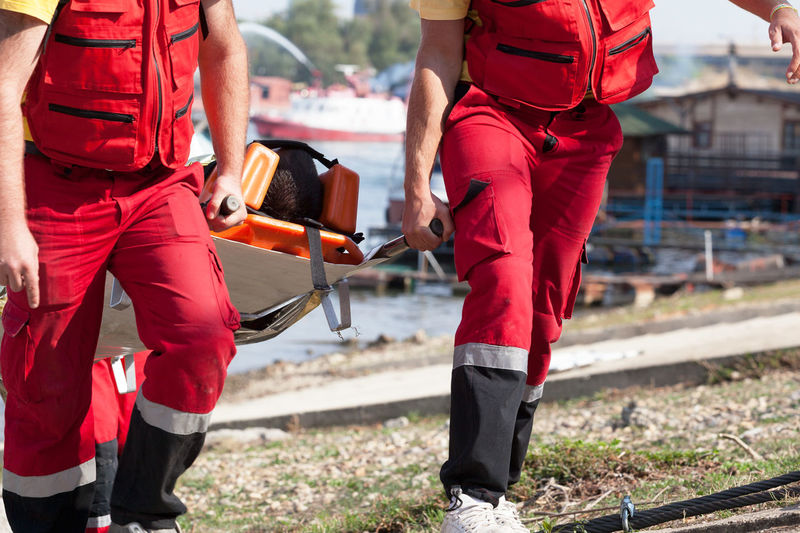 Paramedics carrying drowning patient on a stretcher Safety Uniform Paramedic Rescue Lifesaver First Aid Training Drowning Patient Victim Accidents And Disasters Stretcher Immobilization Reanimation Resuscitation Aid Helping Accident Rescuer Carrying Carry Assistance Emergency Drowned