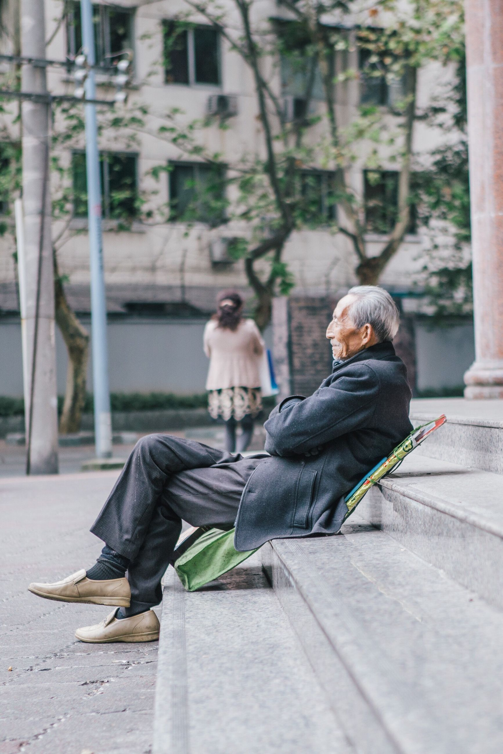 sitting, full length, togetherness, casual clothing, focus on foreground, city, selective focus, person, day, outdoors, city life, park