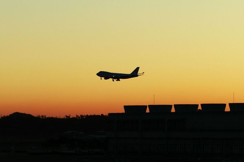 Low angle view of silhouette airplane landing against orange sky