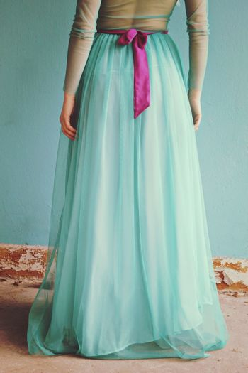 Low Section Of Woman In Turquoise Dress Standing Against Wall