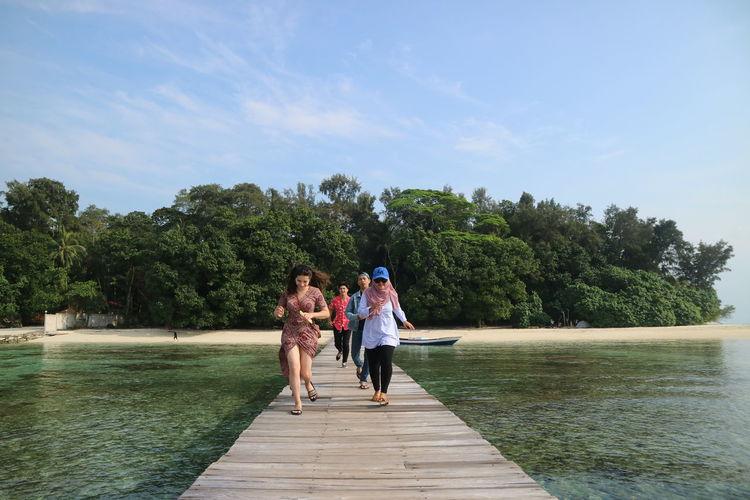 Women walking on riverbank against sky