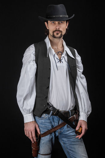 Handsome young man. This is an American cowboy. A vow to a white shirt, brown waistcoat and blue jeans. Black shoes on the feet. Carries a shtyapa, on a belt two pistols. The hair is of medium length; on the face is a beard and mustache. Authentic photo. Culture of America. Cowboy Wild West America American Gun National Authentic Moments Lifestyles Lifestyle One Person Candid Authentic Black Background Hat Three Quarter Length Front View Standing Men Cut Out Males  Casual Clothing Occupation Adult Beard Fashion