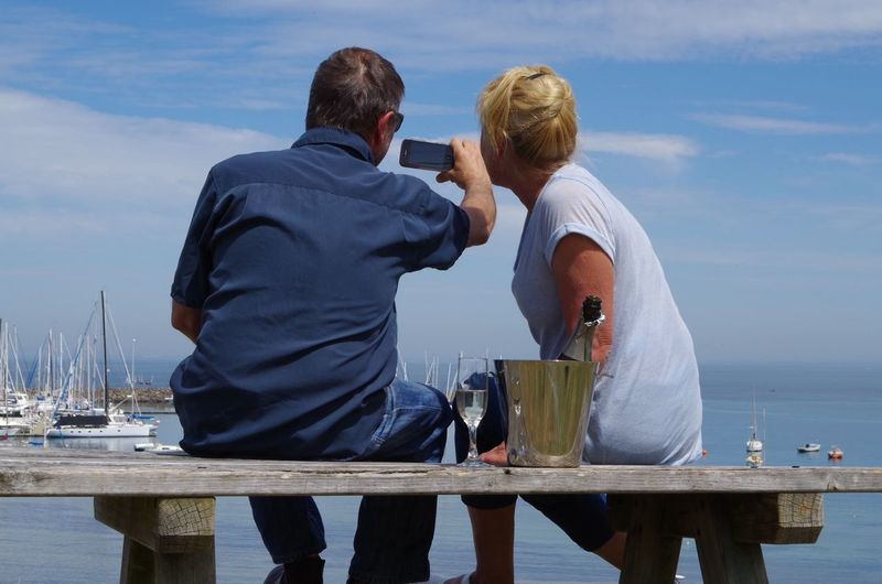 Rear View Of Couple Taking Selfie While Sitting On Bench Against Lake