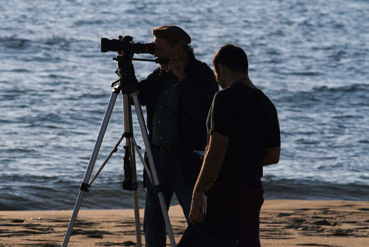 Cinematographic set, backlit cameramen with sunset sea background