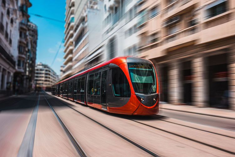 Tramway Moving On Railroad Track Against Buildings In City