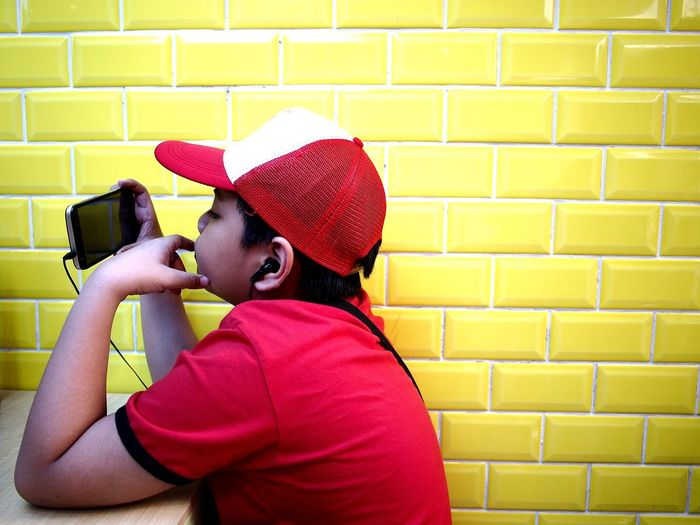 Boy watching mobile phone while sitting at table by yellow wall