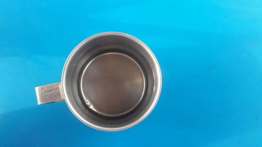 High angle view of black coffee on blue table