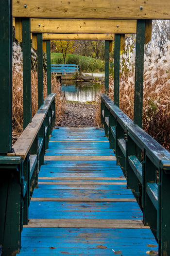 Old Blue Footbridge Leading Towards Pond