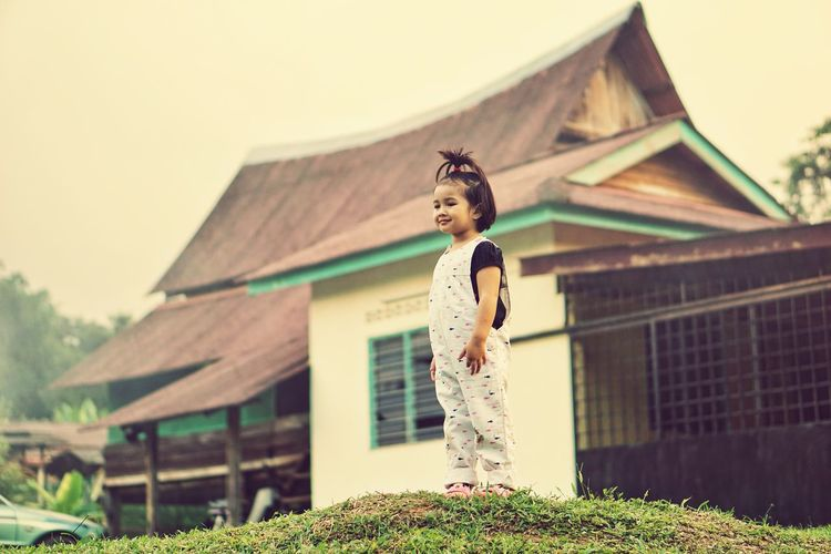 Cute girl standing on field against house