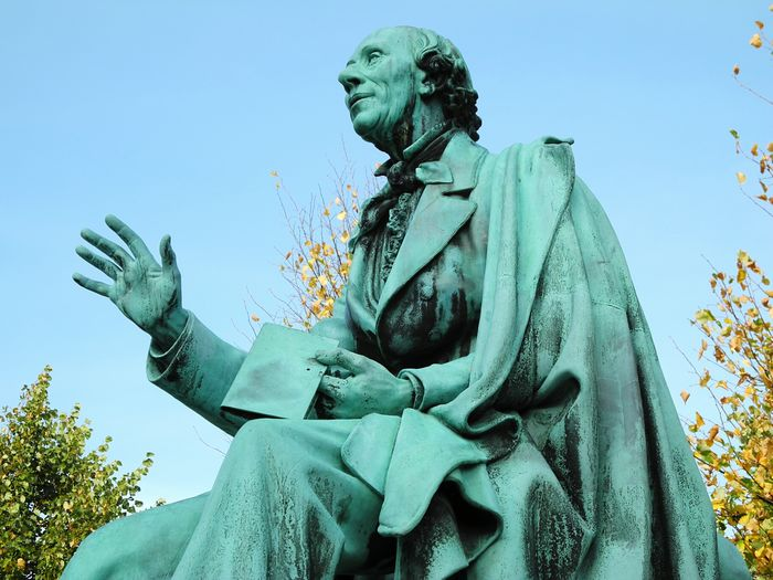 Low angle view of hans christian andersen bronze statue against sky