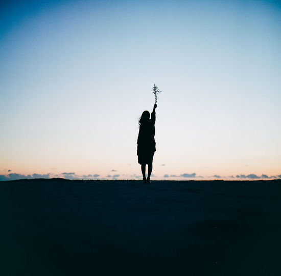 Rear view of silhouette woman standing on field against sky