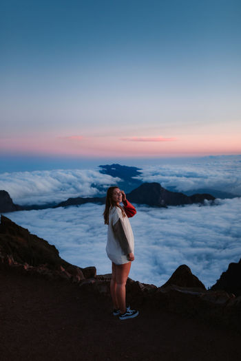 Full length of woman standing on land against sky during sunset