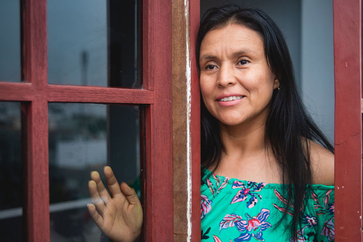 Portrait of woman standing at entrance of window