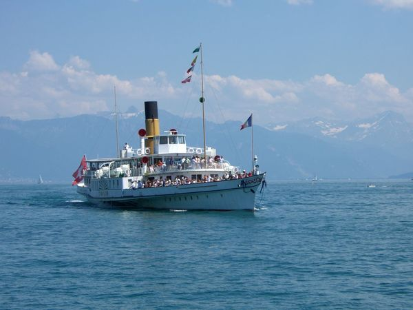 Simplon Boat, Lake Geneva Blue Sky White Clouds Boat Calm Composition Flags Full Frame Geneva Incidental People Lake Lake Geneva Mountains With Snow Rippled Ship Simplon Switzerland Tourist Attraction  Tranquility Water