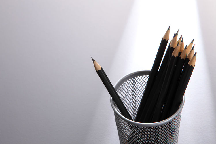 High Angle View Of Pencils In Container Against Gray Background