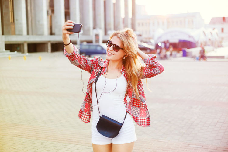 Young woman taking selfie while standing in city