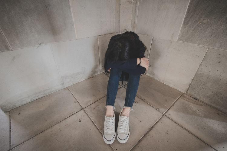 Full length of sad woman sitting on floor