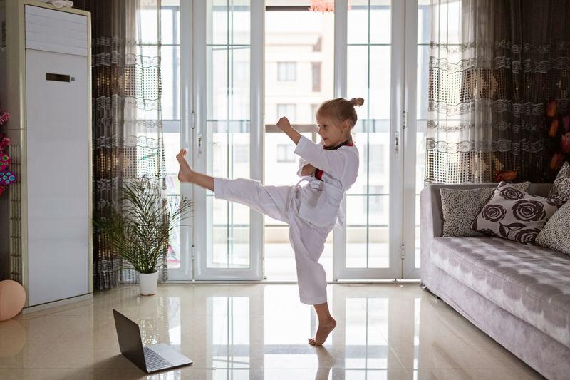 Full length of girl practicing taekwondo at home