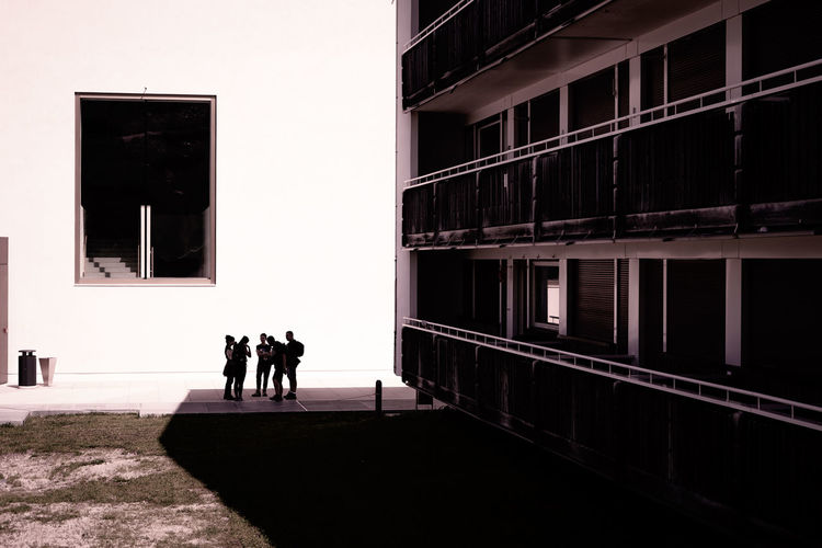 Silhouette people walking on building