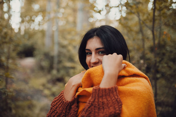 Portrait of young woman standing in forest during autumn