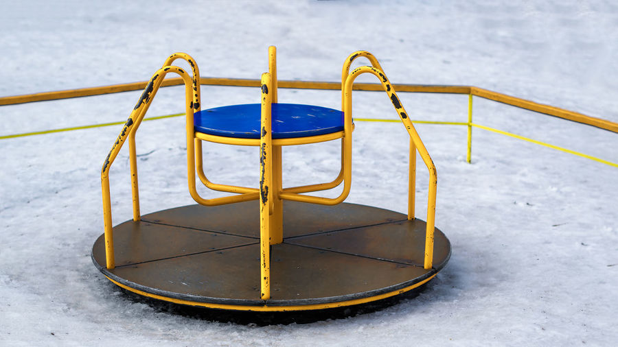 Merry-go-round in snow covered playground