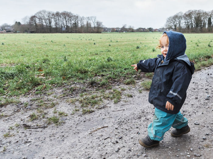 Happy toddler girl pointing on field on a rainy day– Kempen, Germany Exploring Field Footpath Happiness Happy Hiking Wanderlust Winter Child Childhood Children Only First Steps Full Length Germany Hood - Clothing Mud One Person Outdoors Pointing Rural Scene Side View Toddler  Toddlerlife Walking Warm Clothing