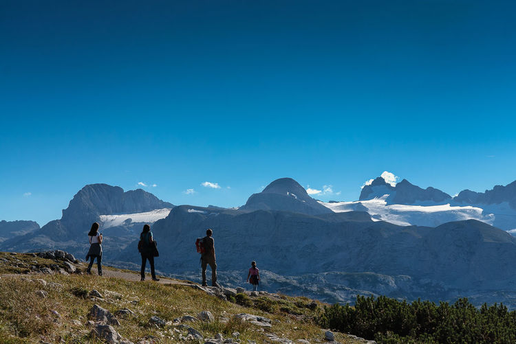 People on mountain against clear blue sky