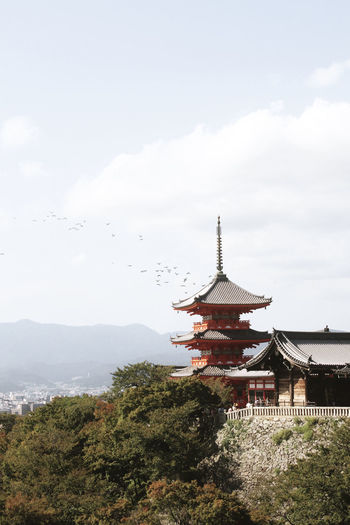 Low angle view of pagoda by building against sky