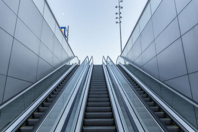 Low angle view of escalator against sky