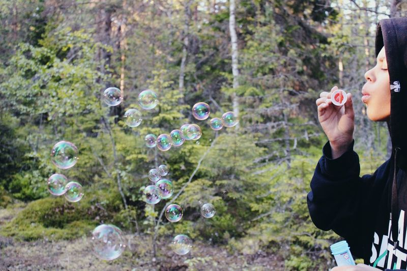 One Person Real People Leisure Activity Lifestyles Plant Nature Day Holding Standing Tree Bubble Land Fragility Blowing Bubble Wand Outdoors Growth Adult Vulnerability