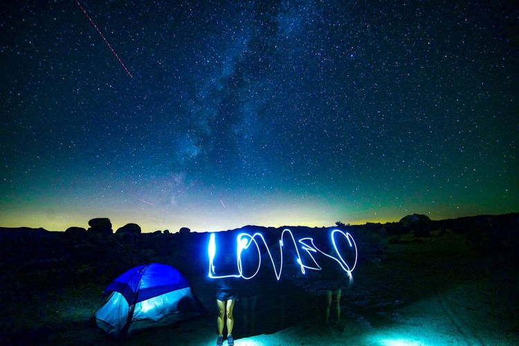 Light painting by tent against sky at night