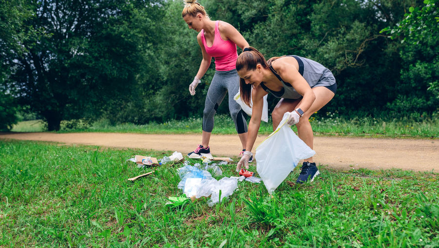 Full length of happy women picking up garbage while crouching on grass against trees