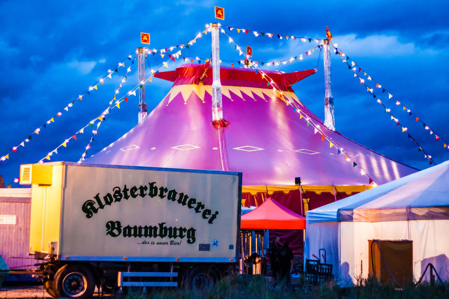 Circus Zirkus Architecture Blue Built Structure Bunting Celebration Cloud - Sky Communication Day Decoration Dusk Focus On Foreground Hanging Illuminated Incidental People Lighting Equipment Nature Outdoors Sky Text Varieté Western Script