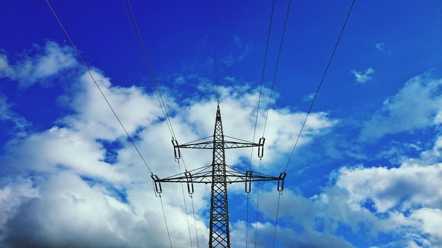 Low angle view of power tower against blue sky