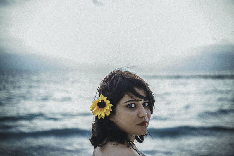 Portrait of young woman against sea