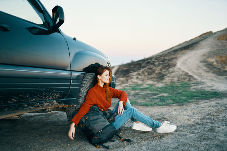 Full length of woman sitting on car against sky