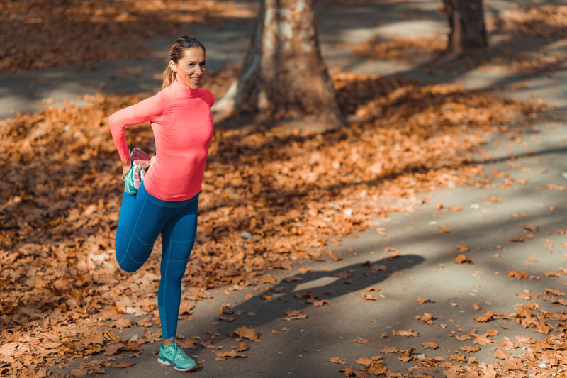 Smiling woman stretching while standing on footpath in park during autumn